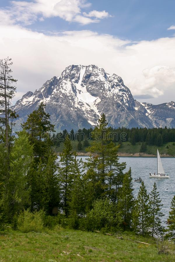 Segelboot auf Jenny Lake mit schneebedecktem Berg Moran im Hintergrund lizenzfreie stockbilder