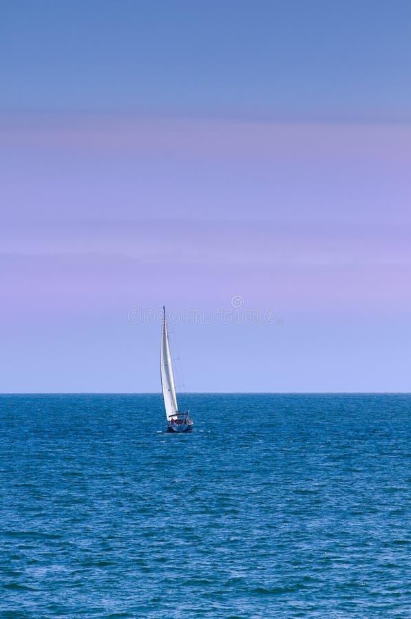 Segelboot auf Ozean an der Dämmerung lizenzfreie stockfotos