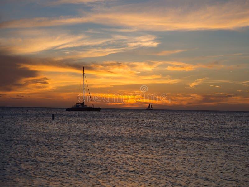 Segelboot, das durch einen Sonnenuntergang ?berschreitet stockbild