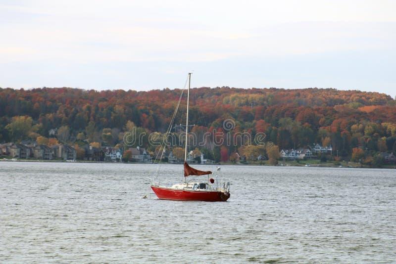 Segelboot im See während des Falles in Chalevoix lizenzfreie stockbilder