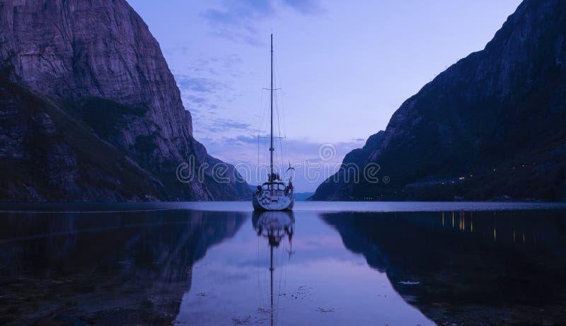 Segelboot lösen herein Fjord mit ruhigem Wasser an der Dämmerung auf stockfotos
