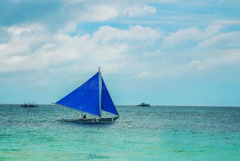 Segelboot mit einem blauen Segel auf einem Hintergrund von Wolken, Boracay-Insel, Philippinen lizenzfreies stockbild