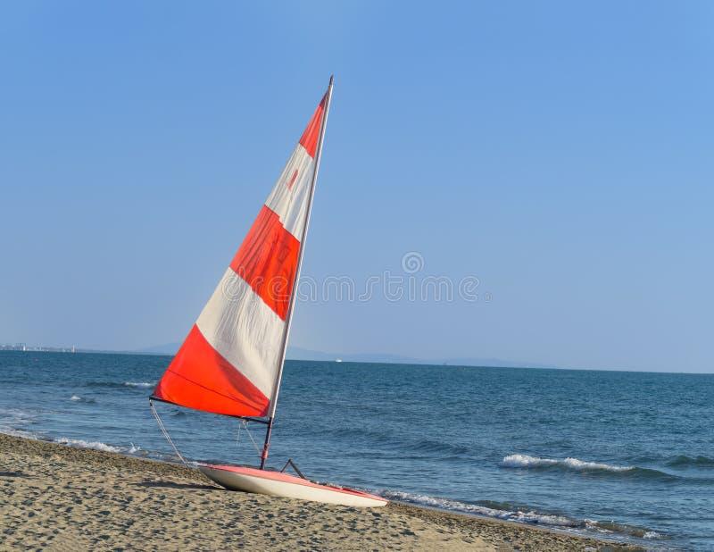 Segelboot mit rotem und weißem buntem Segel auf dem Strand lizenzfreie stockfotografie