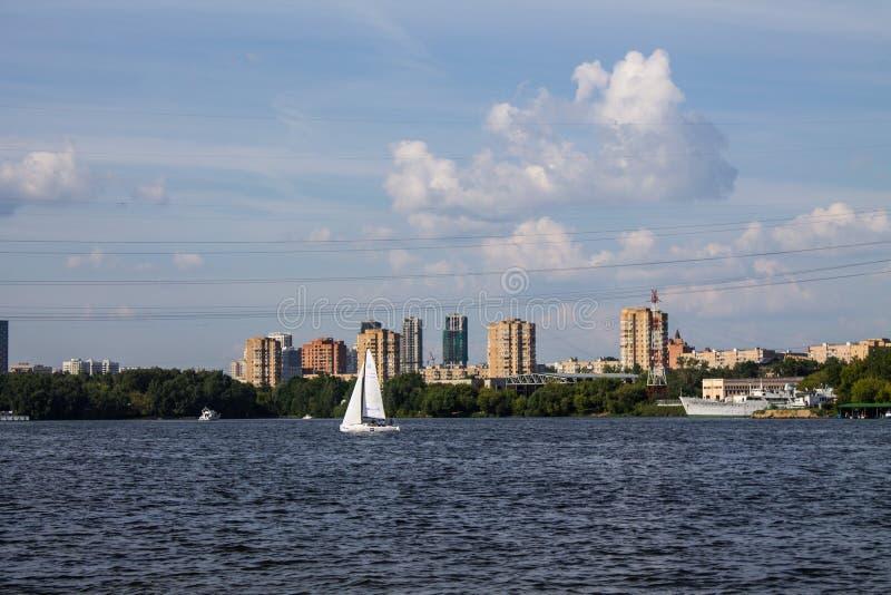 Segelboot mit weißen Segeln auf dem Wasser des Khimki-Reservoirs an einem Sommertag stockfoto
