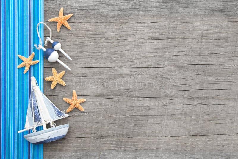 Segelboot und Starfishes auf hölzernem schäbigem schickem Hintergrund lizenzfreie stockfotografie