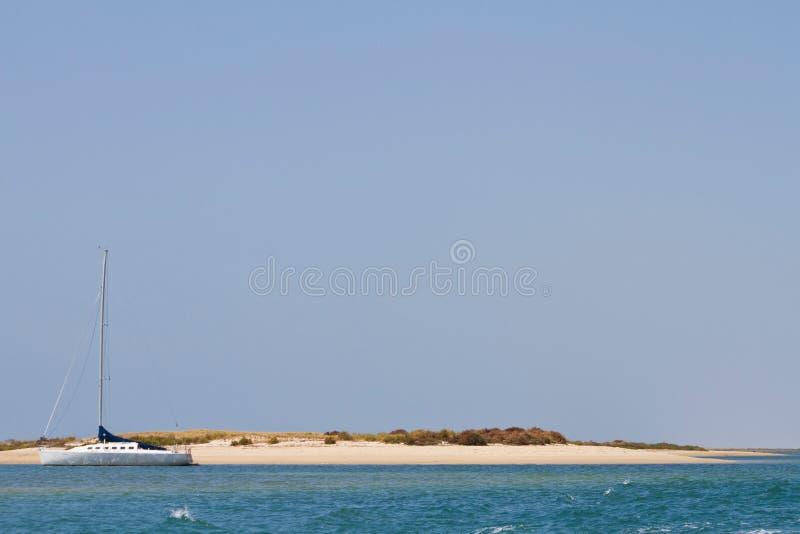 Segelboot und verlassene Insel lizenzfreie stockbilder