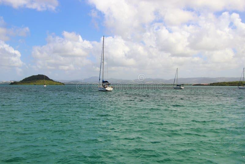 Segelboote auf dem Ozean mit einem schönen blauen Himmel und geschwollenen weißen einem Wolkenhintergrund stockbilder