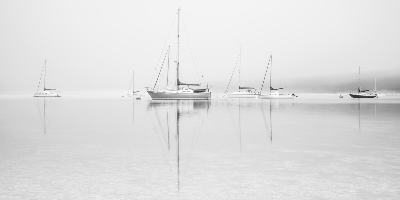 Segelboote auf nebelhaftem See stockfotos