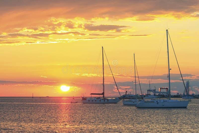 Segelboote bei orange Sonnenuntergang lizenzfreie stockfotos