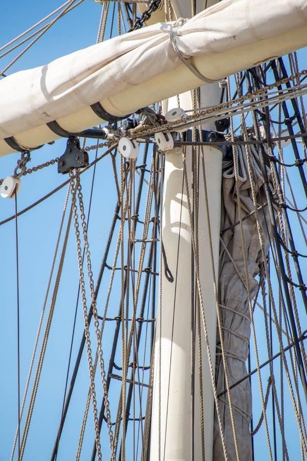 Segelbootmaste, Takelung und gerollt herauf Segel lizenzfreie stockfotografie
