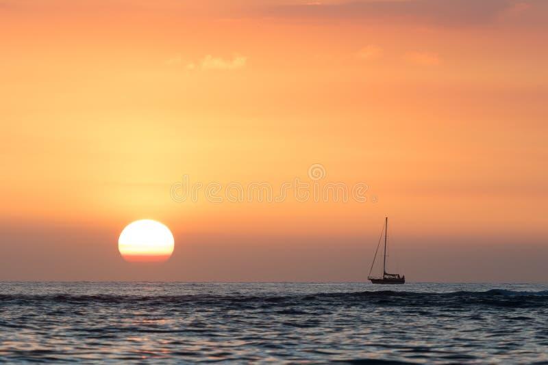 Segelbootsonnenuntergang mit orange Himmel stockfoto