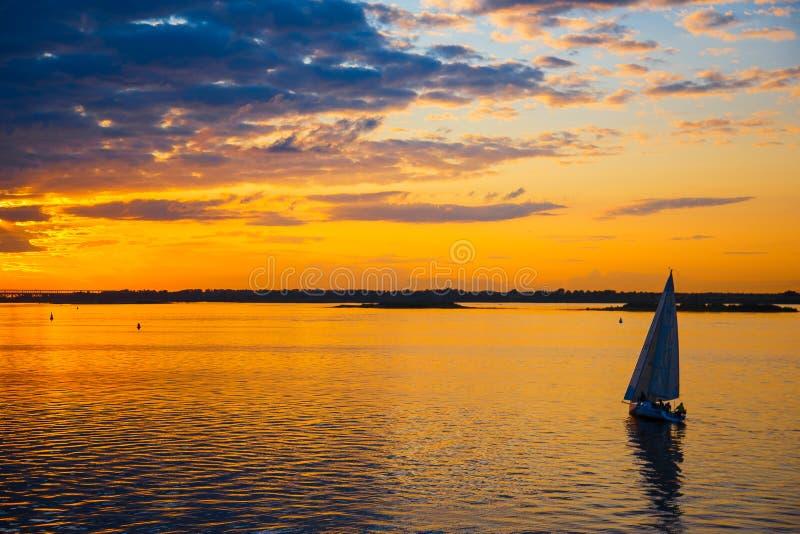 Segeljacht bei Sonnenuntergang im Meer segeln yachting lizenzfreies stockbild