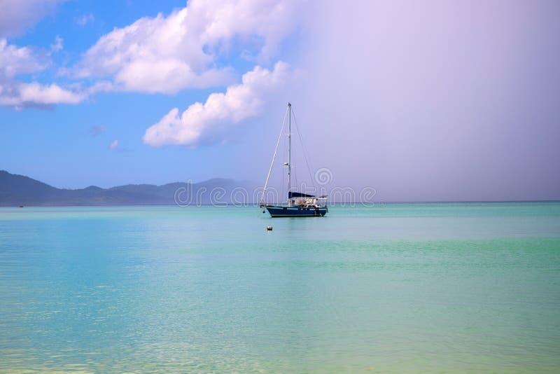 Segeljacht im Türkisblaumeer unter regnerischer Wolke Tropischer Sturm in der Marinelagune Regenwolke auf exotischer Küste lizenzfreie stockbilder
