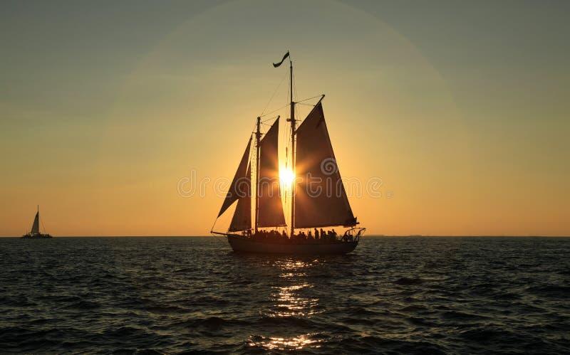 Segeln in den Sonnenuntergang stockbilder