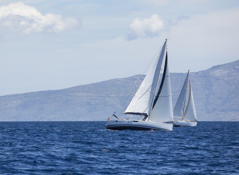 Segeln in den Wind durch die Wellen in dem Ägäischen Meer in Griechenland Reihen von Luxusyachten am Jachthafendock lizenzfreies stockbild