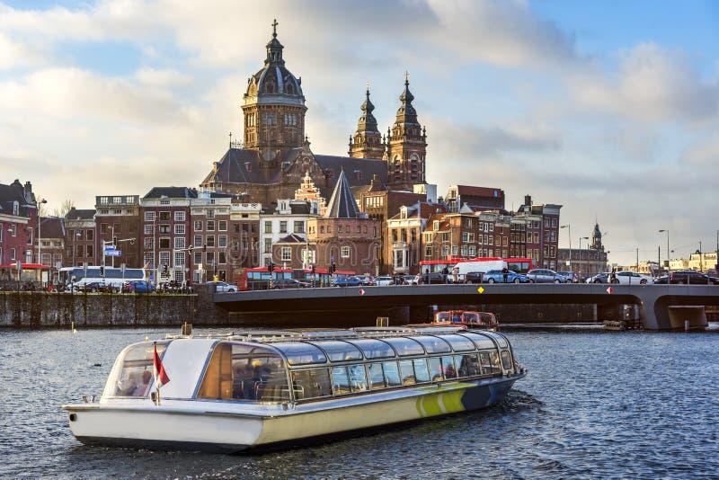 Segeln des touristischen Bootes in der Front das Basilika-Saint Nicolas nachts Amsterdam lizenzfreie stockfotos