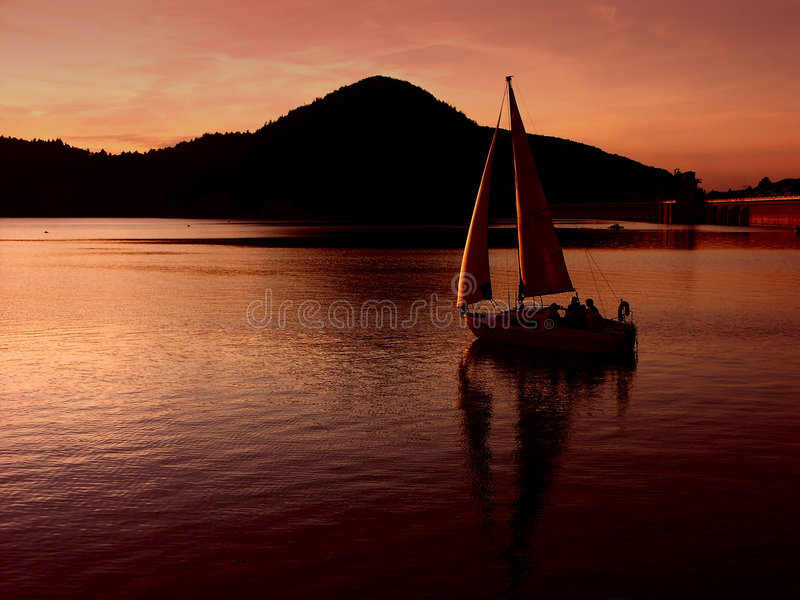 Segeln durch den Sonnenuntergang stockbilder