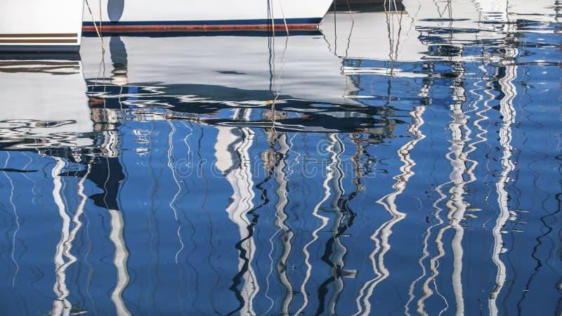segeln Reflexion von Yachtmasten im Wasser des Hafens lizenzfreies stockfoto