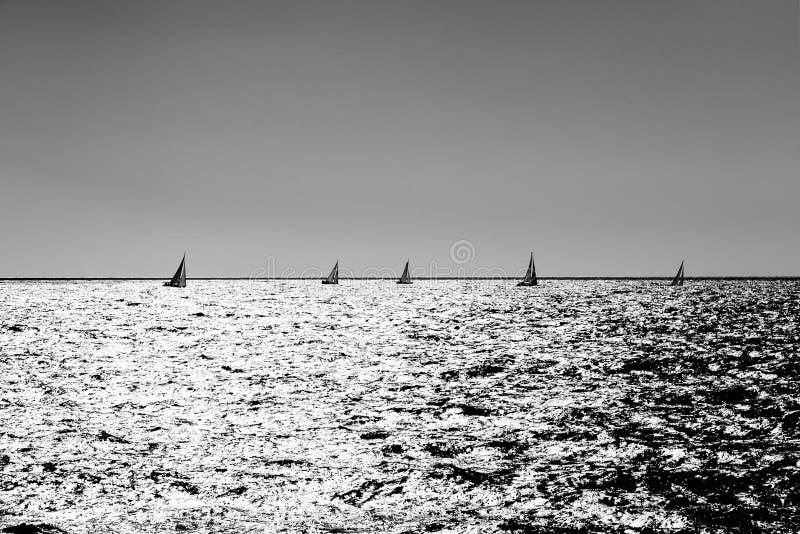 Segeln von laufenden Booten in einem silbernen Meer stockbild