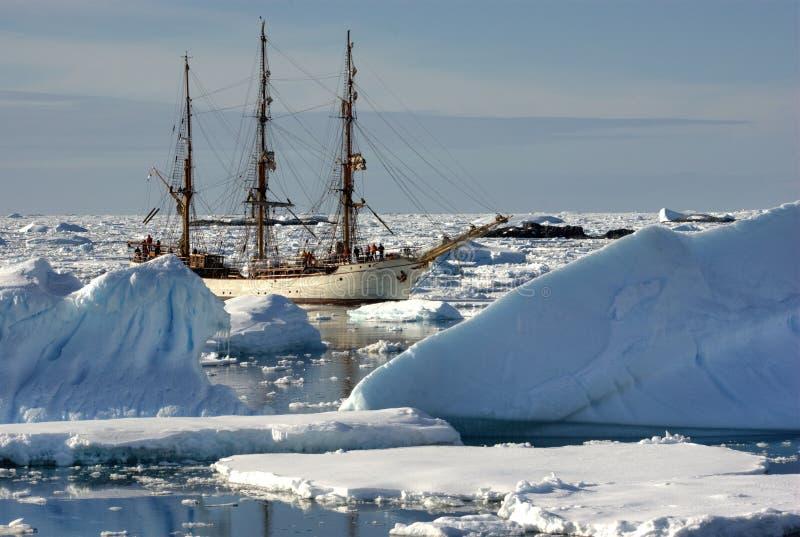 Segelnlieferung unter den Eisbergen lizenzfreie stockfotos
