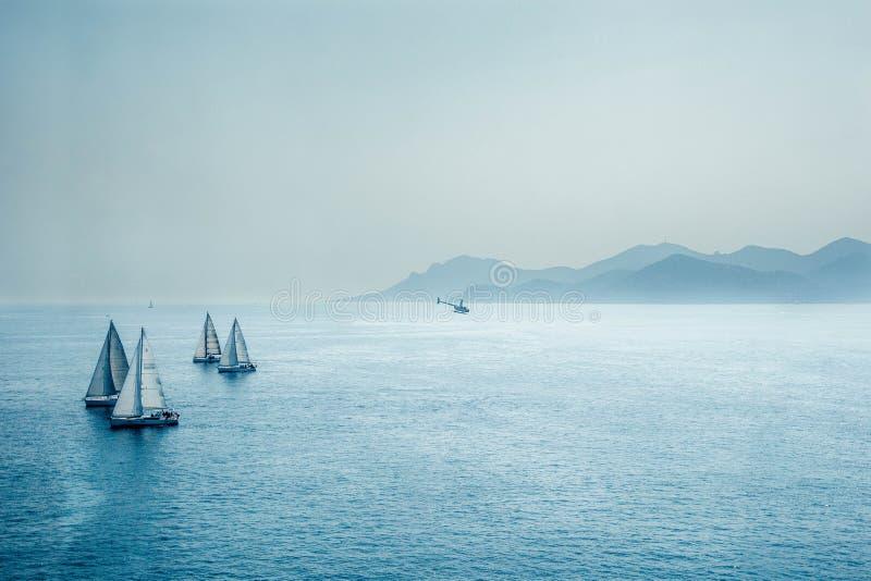 Segelnregatta oder eine Gruppe von laufenden Booten und von Hubschrauber des kleinen Wassers im Mittelmeer, ein Panoramablick mit lizenzfreie stockbilder