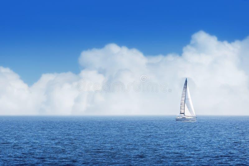 Segelschiff yachts mit weißen Segeln und bewölktem Himmel stockbild