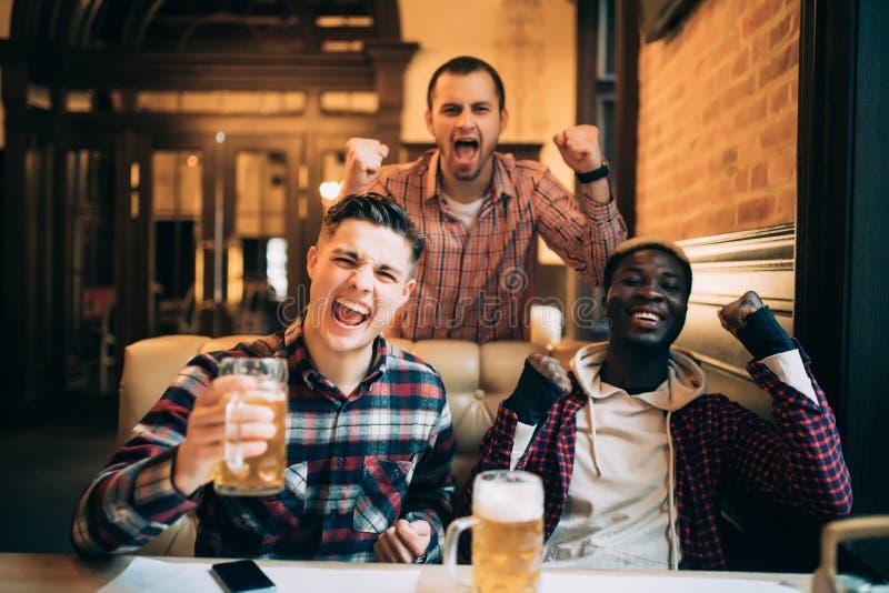 seger Grupp av unga härliga vänner som håller ögonen på TV och hurrar för deras lag, medan vila i bar arkivfoton