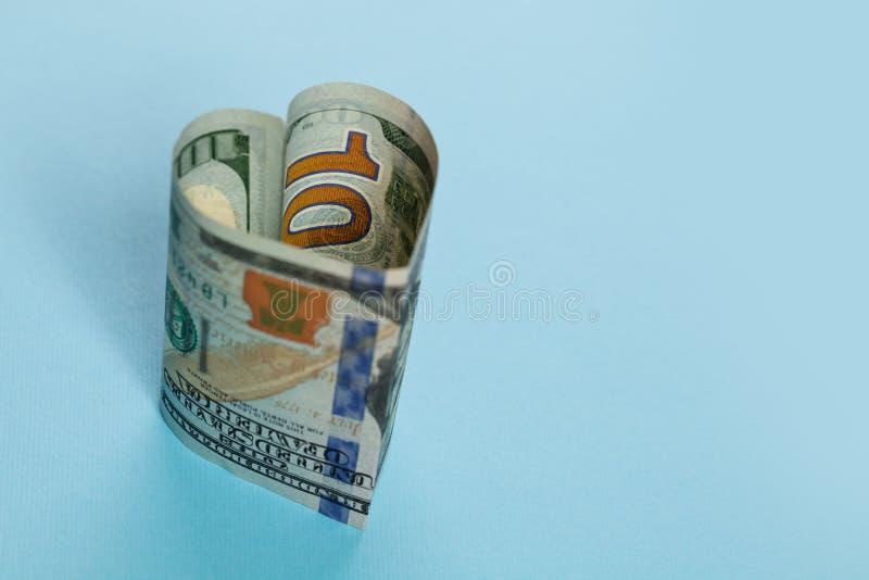 Seger-seger och kommersiellt begrepp för pengarinvesteringvinst 100 US dollar form för hjärta för kassapengarsedel på blå bakgrun fotografering för bildbyråer