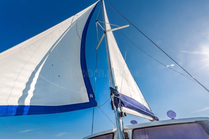 Segla av en segelbåt mot himmel med solstrålar fotografering för bildbyråer