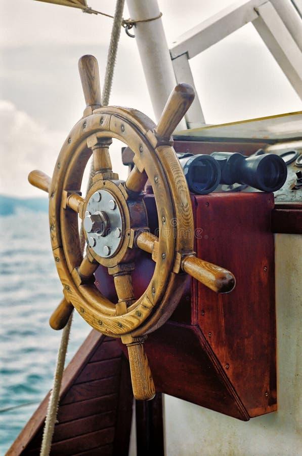 Segla den övre sikten för styrninghjulet och för det vertikala slutet för kikare på havsbakgrund royaltyfri bild