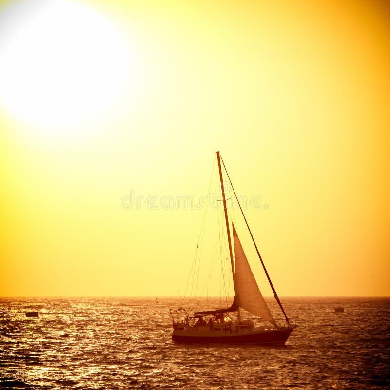 Segla fartyget mot havssolnedgång royaltyfri bild