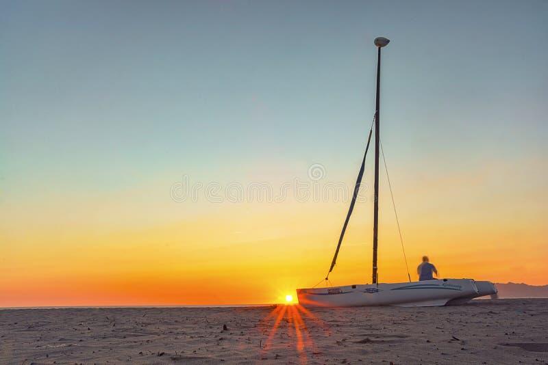 Segla fartyget och solnedgången på stranden arkivbilder