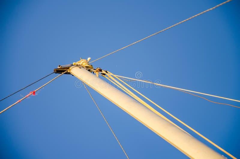 Segla fartygmasten som stödjer, hamparep, blå himmel Minimalist maritimt tema Historia av vattentransport royaltyfri foto