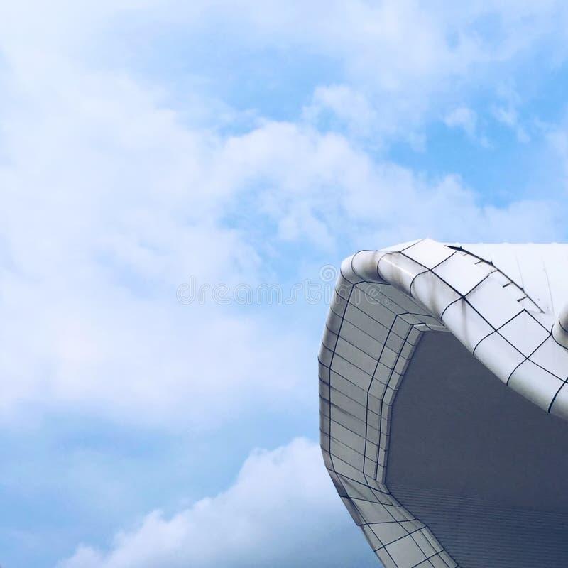 Segla på den blåa himlen, modern arkitektur, det vita taket på den blåa molniga himlen arkivfoton
