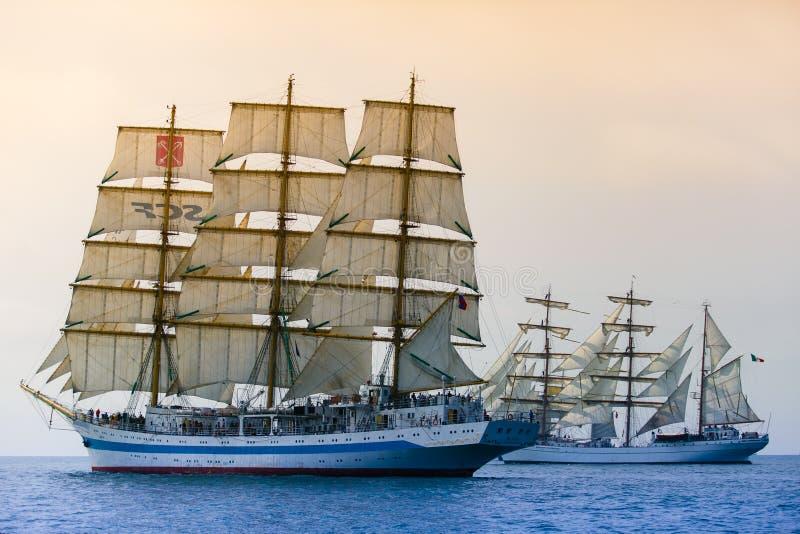 Segla skepp som passerar till och med havet isolerad white för konkurrens begrepp Gemensamt syfte royaltyfria foton