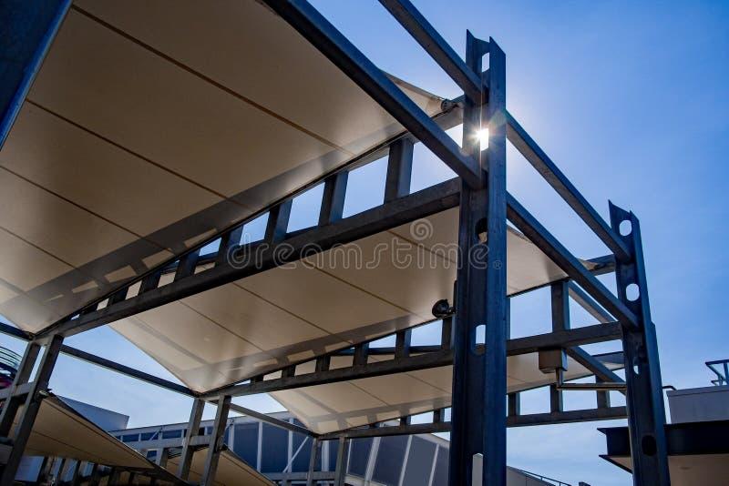 Segla skuggapergolan som göras av galvaniserat stål och den högväxta stående starka strukturen för vitkanfas mot den blåa himlen arkivfoto