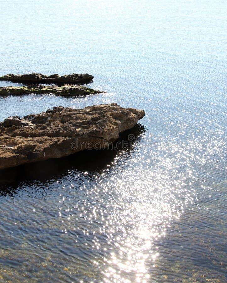 Segla utmed kusten linjen, med vaggar och bevattnar reflexioner arkivfoto