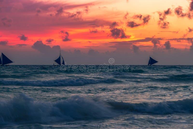 A seglar fartygyachten på horisonten på solnedgångkonturn mot den orange himlen för inställningssolen bak moln royaltyfria foton