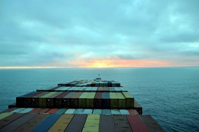Segling för lastbehållareskepp in mot solnedgång på Stilla havet arkivfoto