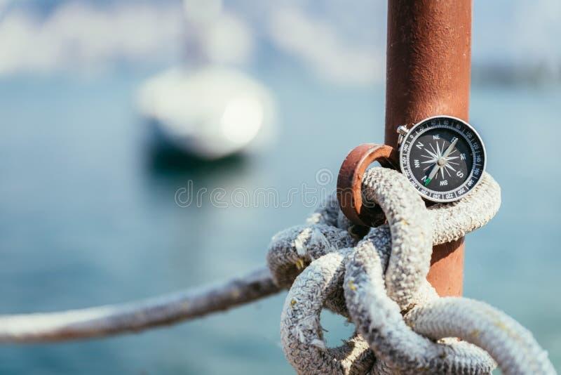 Segling: nautisk kompass p? ett segla rep, pir Segelb?tar i bakgrunden arkivfoton