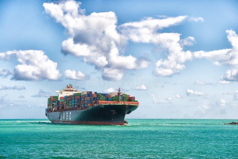 Segling till Miami Jätte- pråmlastbehållare Miami Florida Internationell leverans för trans. Logistik och royaltyfria bilder