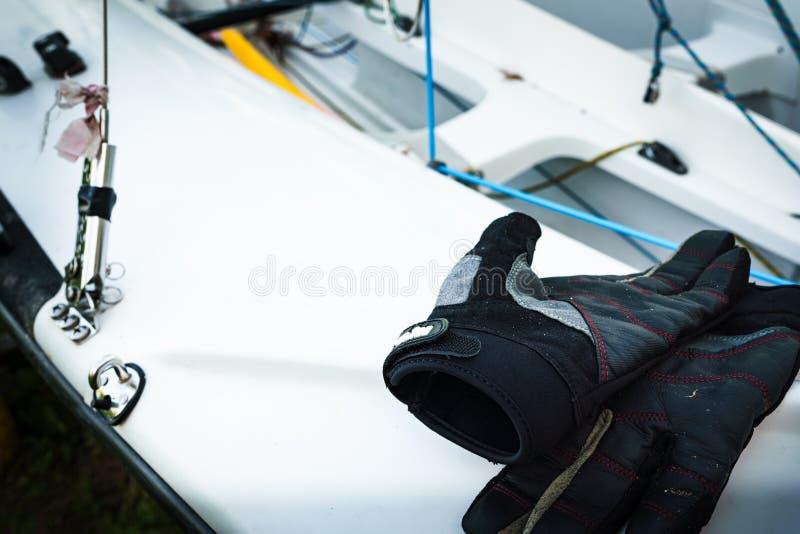 Seglinghandskar på däck av segelbåten vid sjön arkivbilder