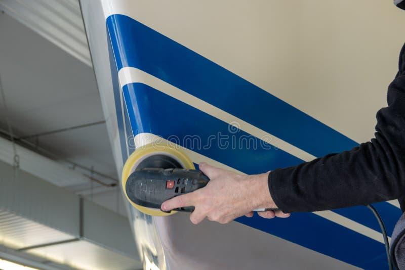 Seglingskeppet står i en färghandel och poleras, når det har målat arkivfoto