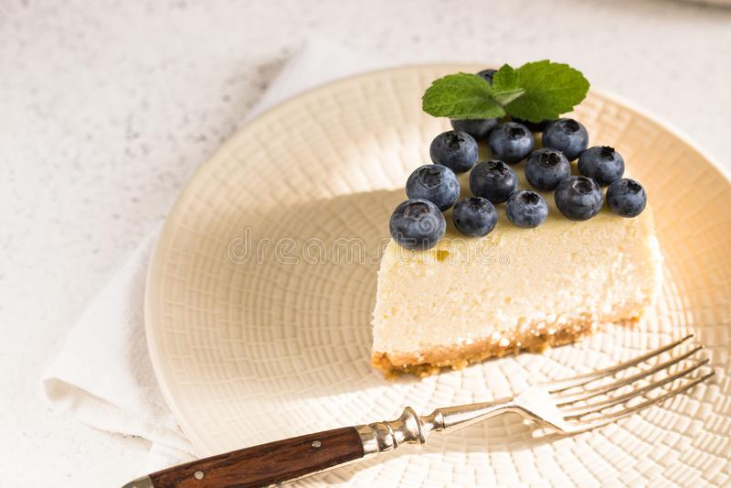 Segment av klassisk ost i New York med blåbär på vit plåt Stängningsvy Hembakverk royaltyfria bilder