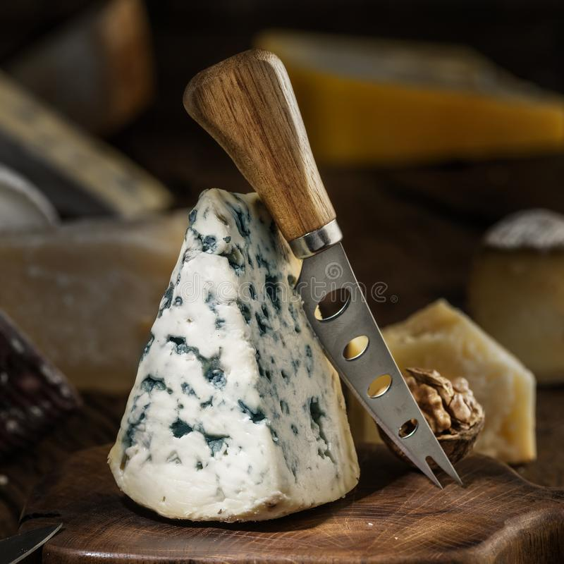 Segment of blue mould cheese and cheese knife on wooden board. Different cheeses at the background stock photography