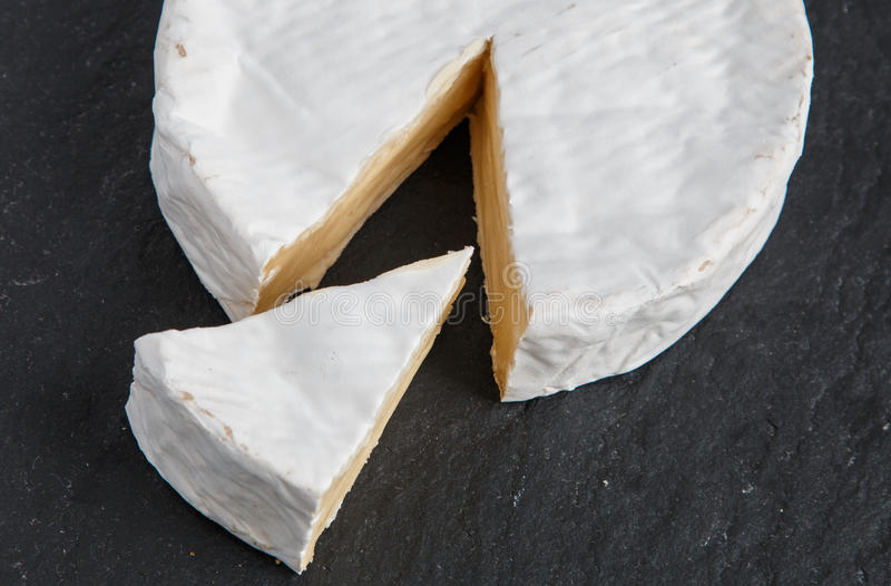 Segment of Brie cheese cut from a whole English Brie cheese stock photography