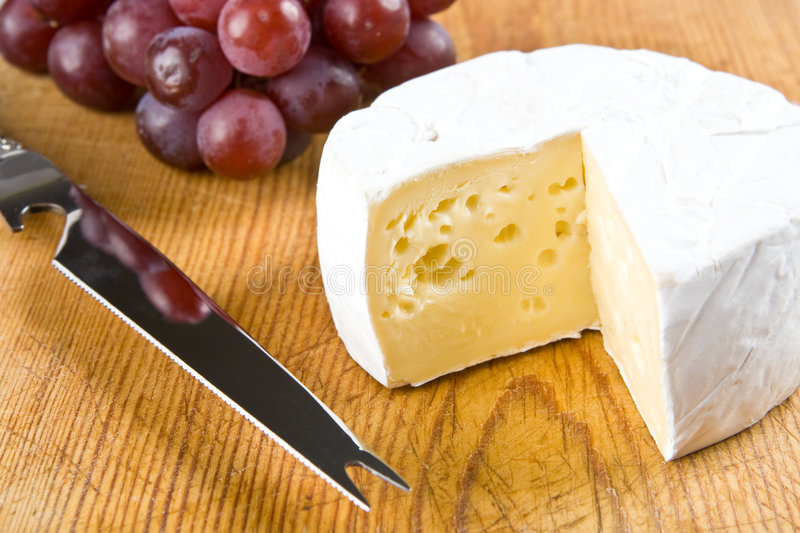 Segment of brie with grapes and a knife. On a board stock photos