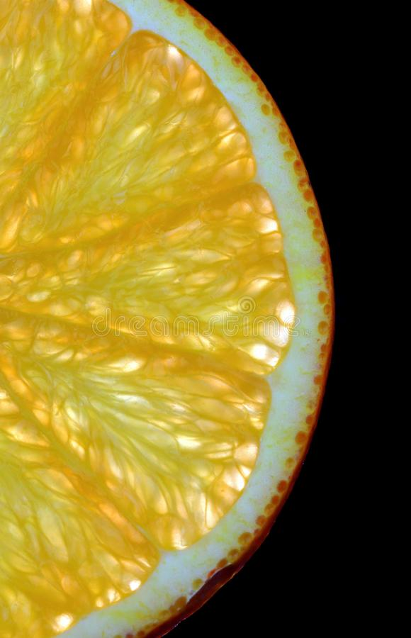 Segment of Orange fruit on a black background bursting with flavour. Juicy segment of a slice of orange with reflection isolated on a black background royalty free stock photography