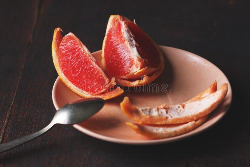 Segmenti di pompelmo rossi e succosi luminosi con una certa buccia che si trova su un piattino immagini stock