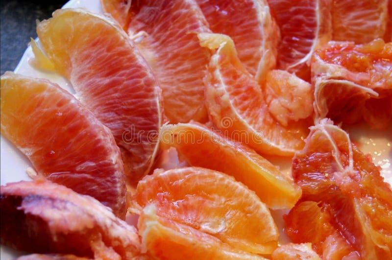 Segmentos da laranja pigmentada em uma placa imagem de stock